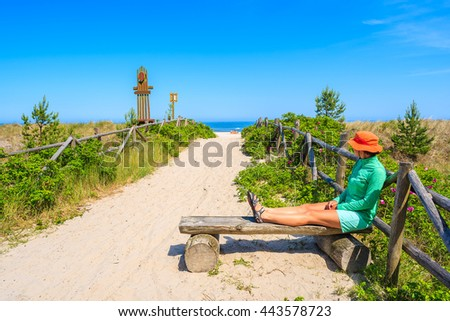 Young woman tourist sitting on bench at entrance to beautiful sandy beach in Lubiatowo coastal village, Baltic Sea, Poland