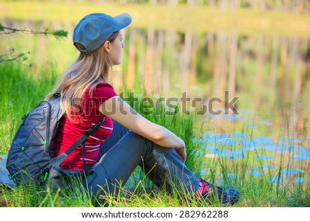 Young woman tourist sitting on grass on pond coast. - stock photo