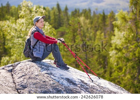 Young woman tourist sitting on mountain top and looking aside on forest. - stock photo