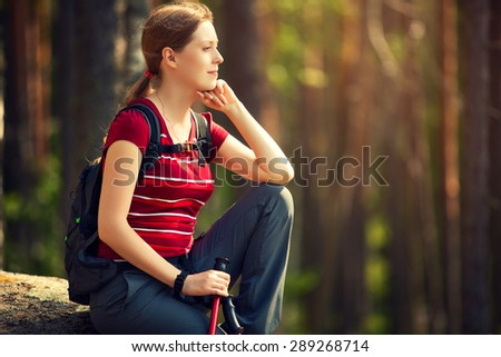 Young woman tourist sitting on stone and looking aside at sunset light. - stock photo