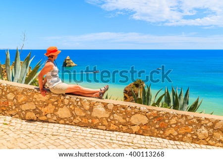 Young woman tourist sitting on stone parapet and looking at beautiful sea near Dona Ana beach, Portugal - stock photo