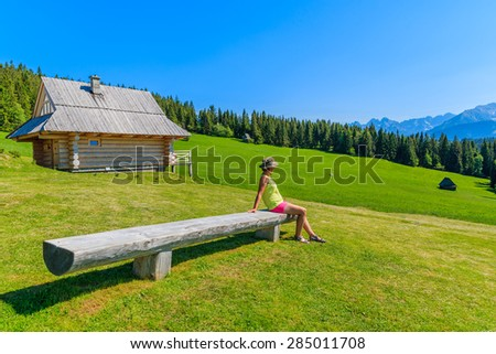 Young woman tourist sitting on wooden bench on green meadow and looking at Tatra Mountains, Poland