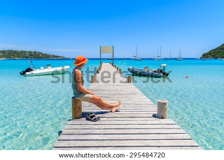 Young woman tourist sitting on wooden jetty in Santa Giulia marina with turquoise sea water, Corsica island, France