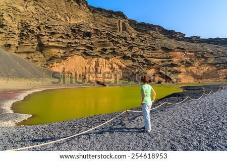 Young woman tourist standing by green water of Lago Verde, El Golfo, Lanzarote, Canary Islands, Spain