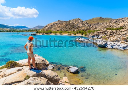 Young woman tourist standing on a rock and looking at beautiful Kolymbithres beach, Paros island, Greece