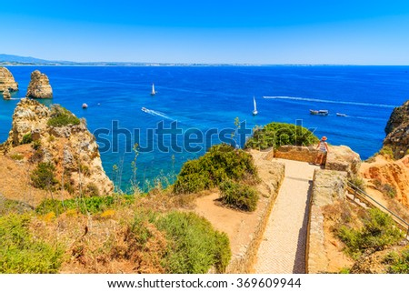 Young woman tourist standing on a viewpoint and looking at blue sea, Ponta da Piedade, Portugal