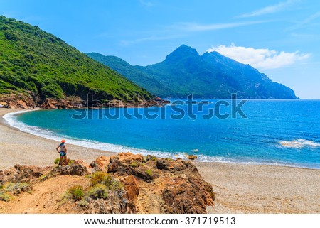 Young woman tourist standing on beautiful secluded beach with azure sea water near Girolata bay, Corsica island, France