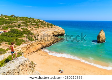 Young woman tourist standing on cliff and looking at beautiful beach near Carvoeiro town, Algarve region, Portugal