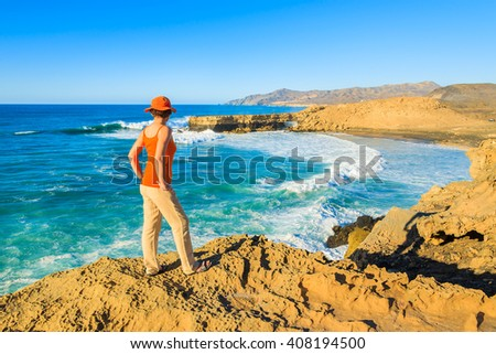 Young woman tourist standing on cliff and looking at beautiful sea bay, Fuerteventura island, Spain