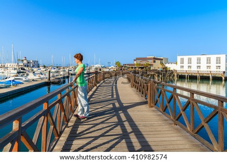 Young woman tourist standing on footbridge in Rubicon yacht port. Lanzarote island, Spain