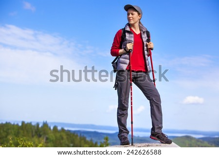 Young woman tourist standing on mountain top and looking aside. - stock photo