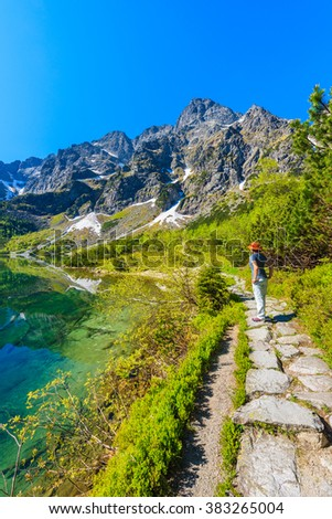 Young woman tourist standing on mountain trail and looking at Morskie Oko lake in summer, Tatra Mountains, Poland