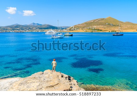 Young woman tourist standing on rock and looking at azure sea with sailing boats on coast of Paros island, Greece