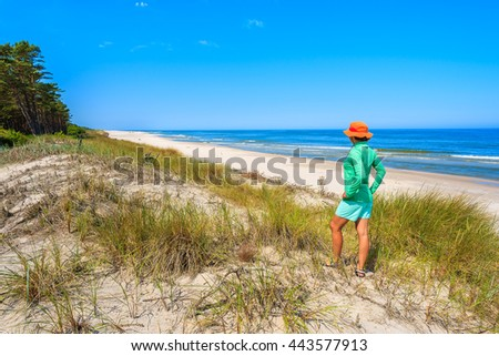 Young woman tourist standing on sand dune and looking at beautiful beach in Lubiatowo coastal village, Baltic Sea, Poland