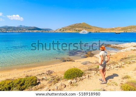 Young woman tourist standing on shore and looking at azure sea with sailing boats on coast of Paros island, Greece