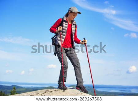 Young woman tourist walking on mountain with sticks. On blue sky background. - stock photo