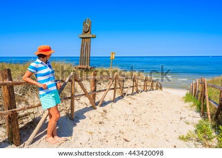 Young woman tourist wearing a hat standing at entrance to idyllic sandy beach in Bialogora coastal village, Baltic Sea, Poland