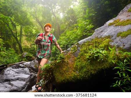 Young woman tourist with a backpack walking along the trail in the rain forest. Lombok, Indonesia. Tourist hiking in the deep jungle - stock photo