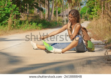 Young woman tourist with backpack and a map in her hands sitting on the road on Koh Phangan island, Thailand.  - stock photo