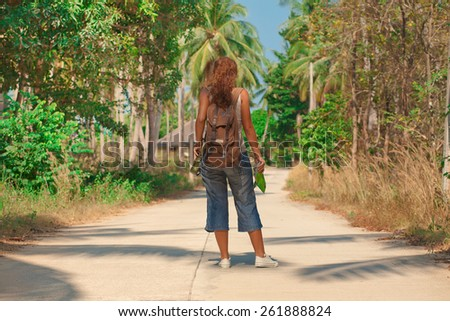 Young woman tourist with backpack and a map in her pocket on the road on Koh Phangan island, Thailand.  - stock photo