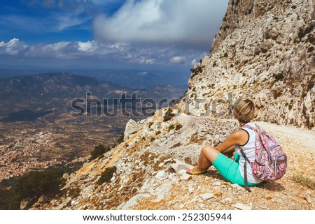 young woman tourist with backpack on background panoramic view from the mountains on the island of Sardinia in clear weather, Monte Corrasi, Italy - stock photo