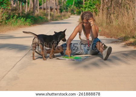 Young woman tourist with the dog sitting on the road on Koh Phangan island, Thailand.  - stock photo