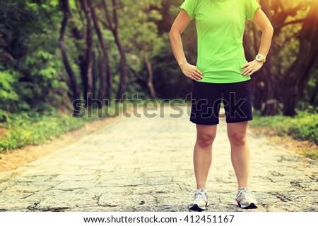 young woman trail runner in forest