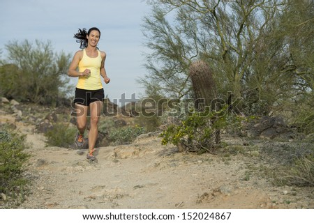 Young woman trail running outdoors at South Mountain Park in Phoenix, Arizona.