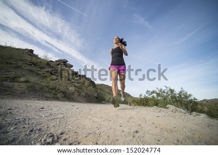 Young woman trail running outdoors at South Mountain Park in Phoenix, Arizona.  Shot from a low angle view. - stock photo