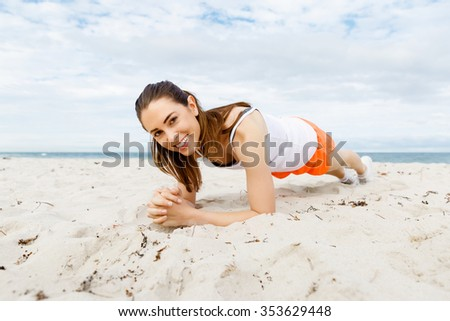 Young woman training alone on beach outside