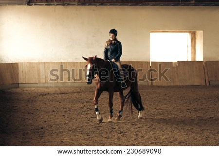 Young woman training brown horse in riding hall - stock photo