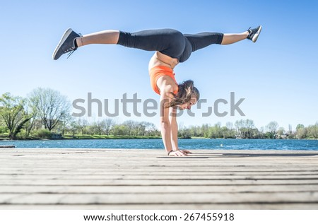 young woman training gymnastic in front of the lakes