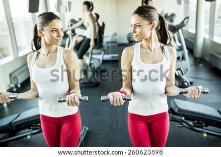 Young woman training in the gym by the mirror - stock photo