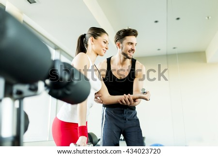 Young woman training in the gym with handsome trainer - stock photo