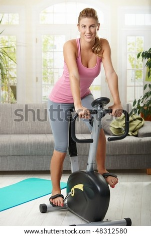 Young woman training on exercise bike at home, smiling. - stock photo