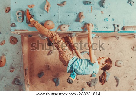 Young woman training on practice climbing wall indoor - stock photo