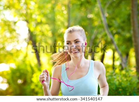 Young woman training outside in the park and listening to music. Sport lifestyle