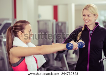 Young woman training with a female personal trainer or fitness instructor as she works out in a gym with dumbbells - stock photo