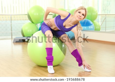Young woman training with gymnastic ball in gym - stock photo