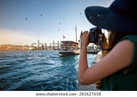 Young woman traveler in green dress and hat enjoying great view of the Bosphorus in Istanbul - stock photo