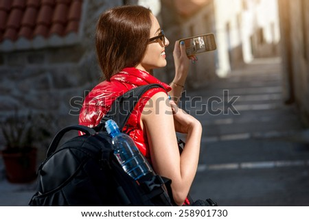 Young woman traveler in red sportswear photographing with smart phone old city street. - stock photo