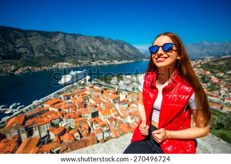 Young woman traveler in red vest with backpack on the Lovcen mountain near the old city Kotor, Montenegro - stock photo