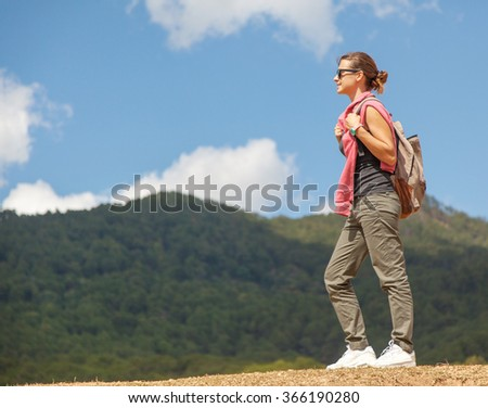 Young woman traveler on a background of mountains and sky. Happiness, freedom, tourism