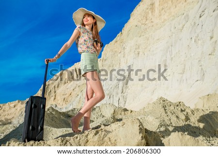 Young woman traveler on the top of sand dunes with baggage and photo camera - stock photo