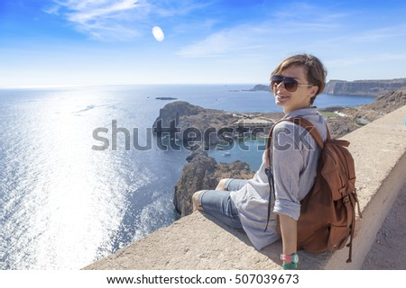 Young woman traveler sitting overlooking the sea. Travel to Greece