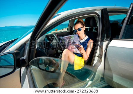 Young woman traveler sitting with paper map in the car and looking where to go on blue sea background - stock photo