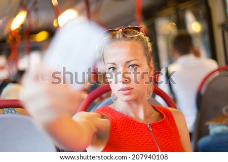 Young woman traveling by bus, having her ticket checked.