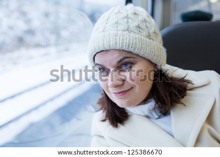Young woman traveling by train and looking out the window outside, while it moving. travel - stock photo