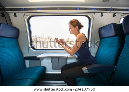 Young woman traveling by train, using her smartphone while sitting on board, alone - stock photo