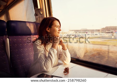 Young woman traveling  looking out the window while sitting in the train. - stock photo